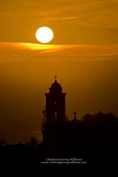 Silhouette of Greek chapel against setting sun